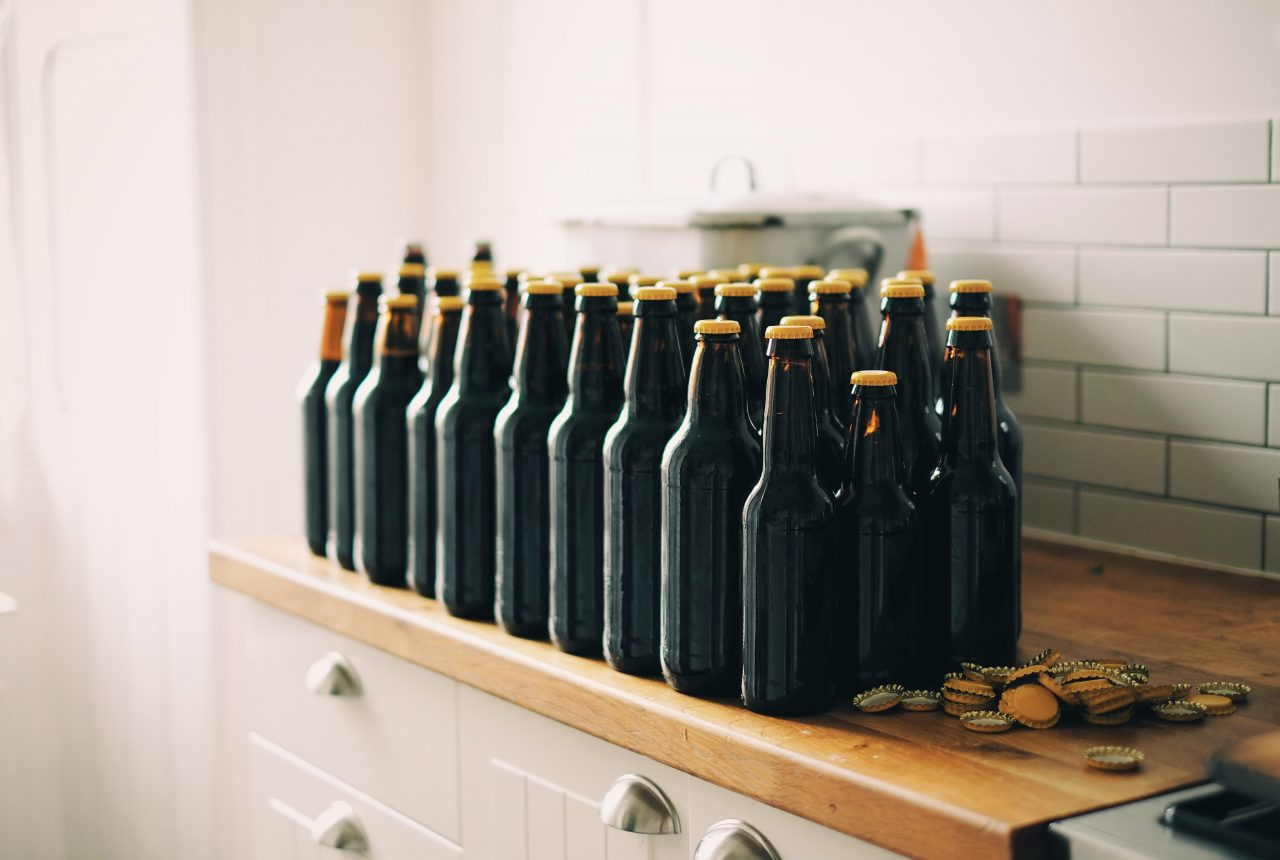 Beer bottles lined up on a shelf with no label